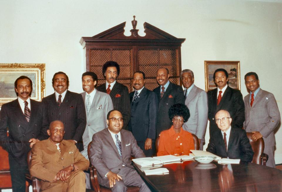 Photo of 9 Black men standing, wearing suits, 3 Black men and one Black woman seated, dressed professionally.