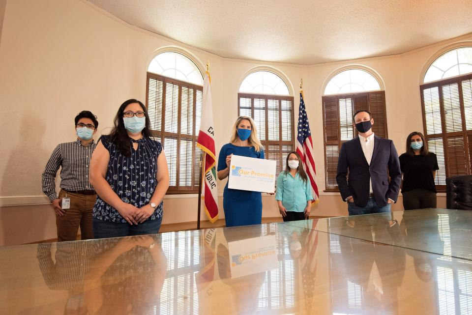 Photo of 6 individuals wearing masks and professional attire. One woman holding an Our Promise sign. CA and US flags in the background.
