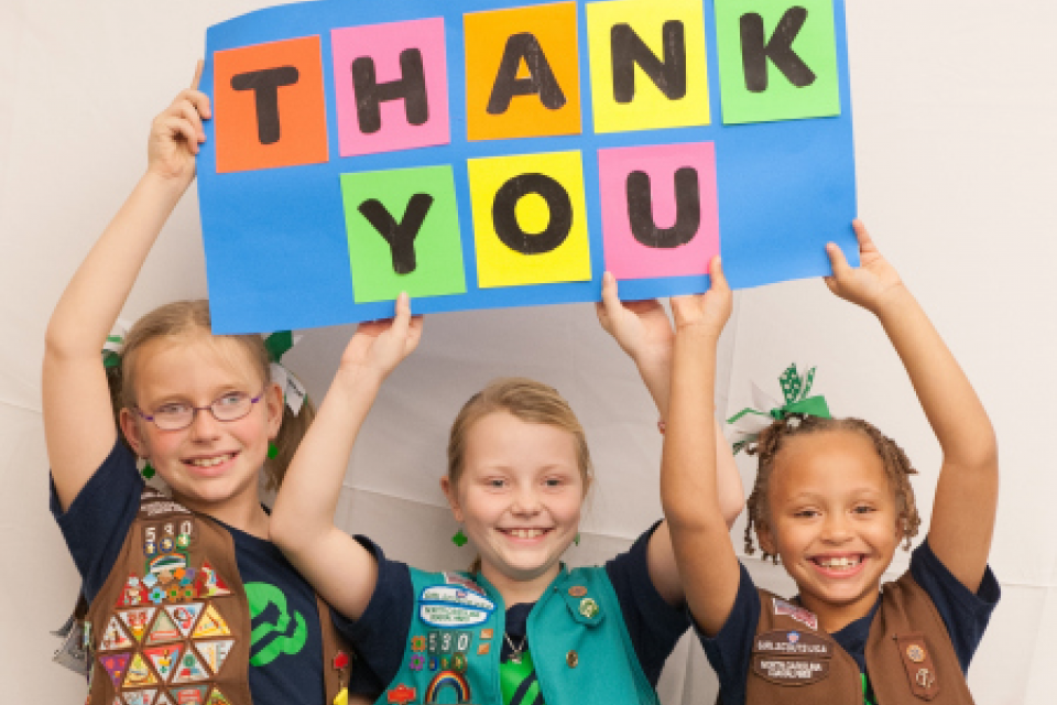 "3 young girls in Girl Scout vests holding a sign that reads, ""THANK YOU"""